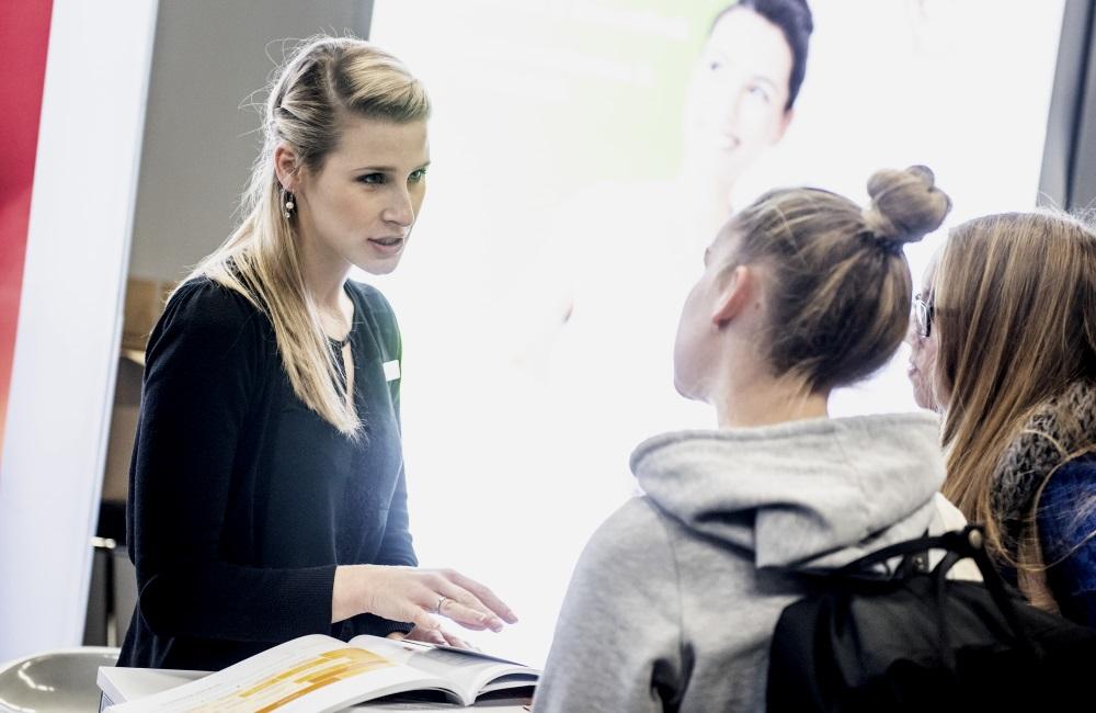 Eine frau berät zwei Schülerinnen auf der Berufe live